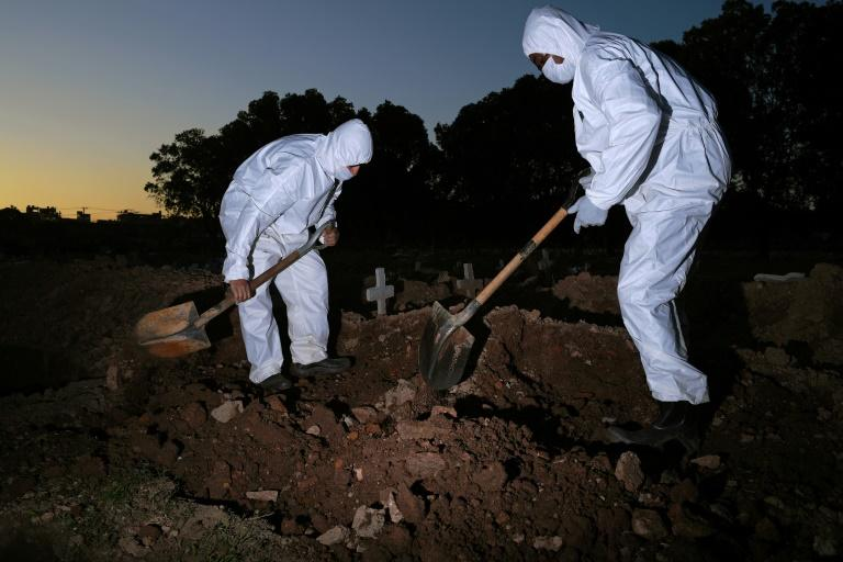Workers wear protective clothing to bury a COVID-19 victim at the Sao Franciso Xavier cemetery in Rio de Janeiro, Brazil on May 29, 2020