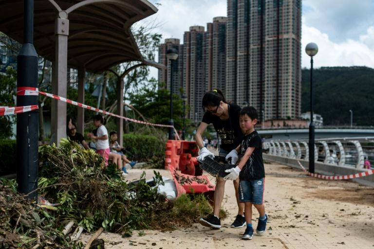 Volunteers pick up debris on the promenade in Tseung Kwan O district in the aftermath of Typhoon Mangkhut