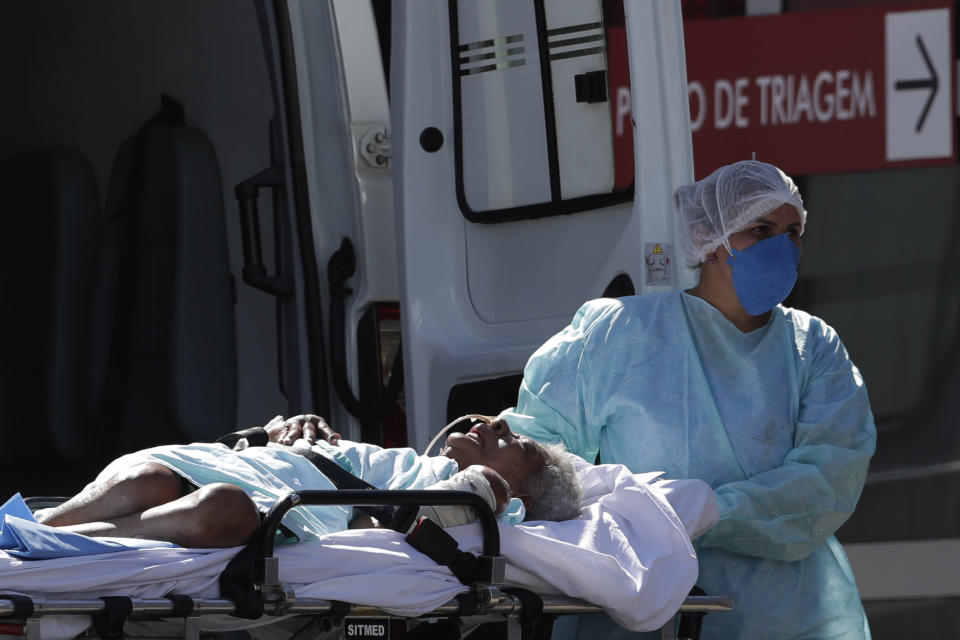 A patient suspected of having COVID-19 is received at the HRAN Hospital in Brasilia, Brazil, Wednesday, March 3, 2021. Brazil dodged the most dire economic forecasts in 2020, but official figures released Wednesday show the COVID-19 pandemic still battered the nation and it continues to dim the outlook for recovery. (AP Photo/Eraldo Peres)
