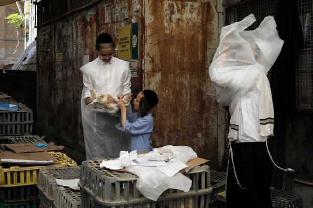 <p>Ultra-Orthodox Jews select a chicken to perform the Kaparot ceremony in the religious neighbourhood of Mea Shearim in Jerusalem on Sept. 27, 2017. The Jewish ritual is supposed to transfer the sins of the past year to the chicken, and is performed before the Day of Atonement, or Yom Kippur, the most important day in the Jewish calendar, which will start this year on September 29 at sunset. (Photo: Menahem Kahana/AFP/Getty Images) </p>