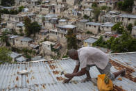 Antony Exilien secures the roof of his house in response to Tropical Storm Elsa, in Port-au-Prince, Haiti, Saturday, July 3, 2021. Elsa brushed past Haiti and the Dominican Republic on Saturday and threatened to unleash flooding and landslides before taking aim at Cuba and Florida. ( AP Photo/Joseph Odelyn)