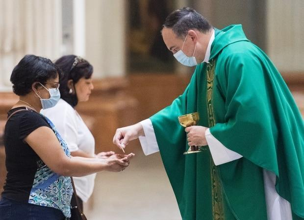 A woman receives communion during mass at the Mary Queen of the World Cathedral in Montreal, Que. The Canadian Conference of Catholic Bishops has urged parishioners to steer clear of viral vector vaccines like the one produced by AstraZeneca. (Graham Hughes/Canadian Press - image credit)