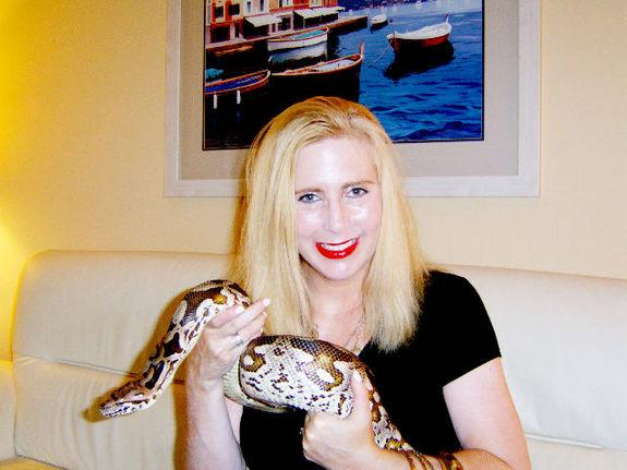 Taryn Hook with Larry, a beloved boa constrictor whose affliction prompted the lifelong keeper of reptiles to get in touch with a researcher who hunts down viruses.