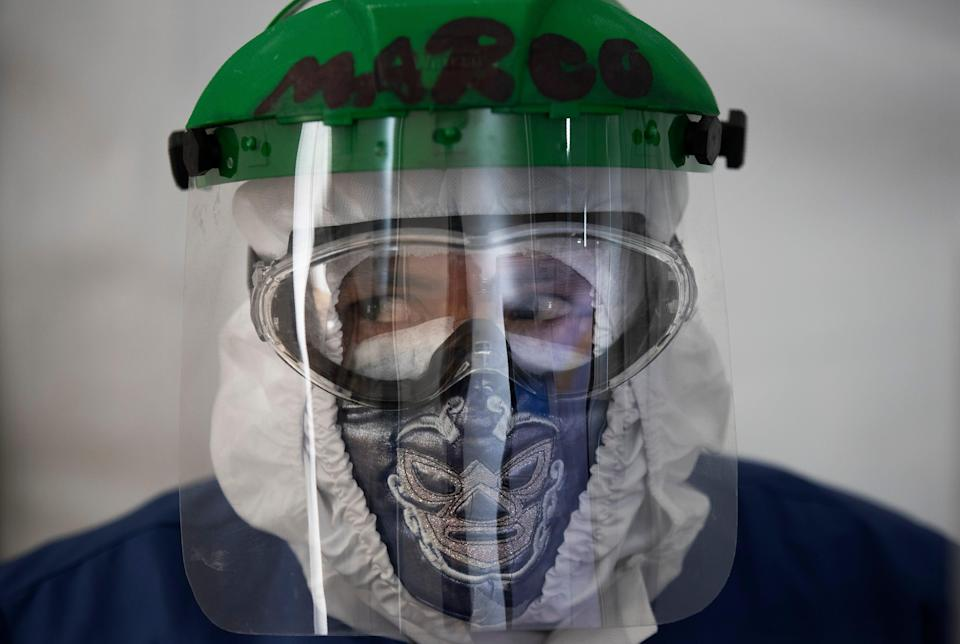 Health care worker Marco Antonio Galicia wears a face mask designed with a Mexican wrestler motif and a protective shield on Thursday at the Ajusco Medio General Hospital in Mexico City.