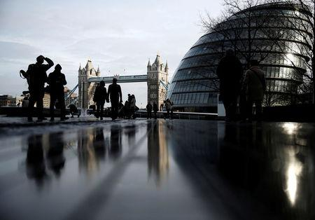 FILE PHOTO: Pedestrians walk near City Hall and Tower Bridge in London