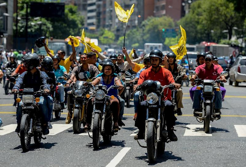 Anti-government protesters ride on motorcycles during a rally calling for a referendum on removing Venezuelan President Nicolas Maduro, in Caracas, on August 4, 2016 (AFP Photo/Federico Parra)