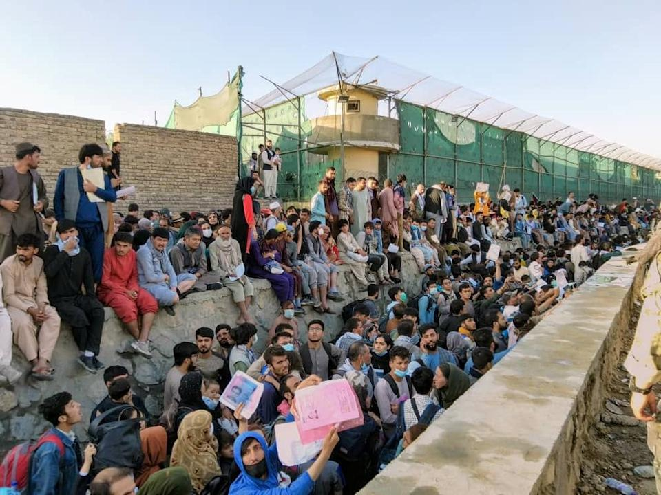 Crowds of people wait outside the airport in Kabul, Afghanistan August 25, 2021 in this picture obtained from social media. (David Martinon/Twitter via Reuters)