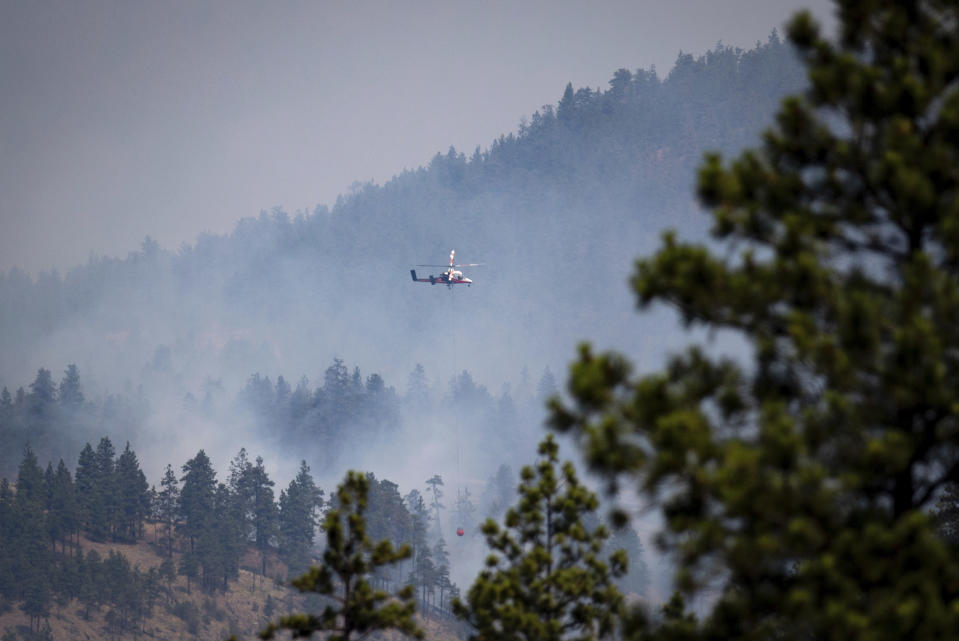 A helicopter pilot prepares to drop water on a wildfire burning in Lytton, B.C., on Friday, July 2, 2021. Officials on Friday hunted for any missing residents of a British Columbia town destroyed by wildfire as Canadian Prime Minister Justin Trudeau offered federal assistance. (Darryl Dyck/The Canadian Press via AP)