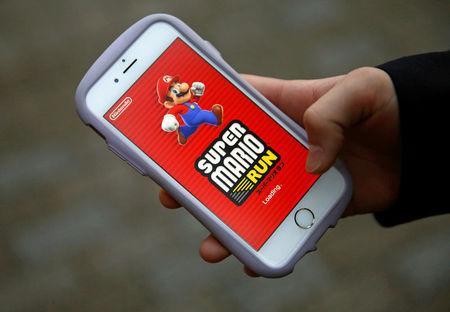"""Takuya Nishya shows Nintendo's """"Super Mario Run"""" game on his smartphone by the request of a photographer in Tokyo"""