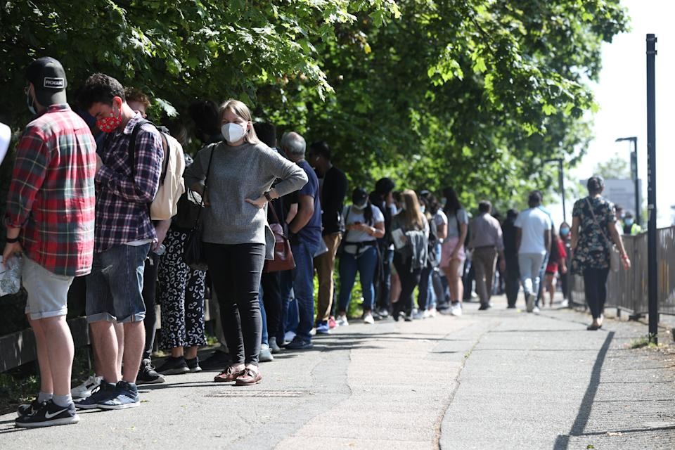 People queuing to go into Belmont Health Centre in Harrow. (PA)