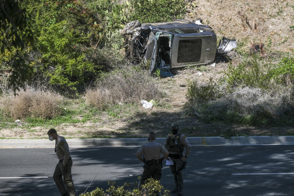 FILE - In this Feb. 23, 2021, file photo a vehicle rests on its side after a rollover accident involving golfer Tiger Woods along a road in the Rancho Palos Verdes suburb of Los Angeles. A man who found Woods unconscious in a mangled SUV last week after the golf star who later told sheriff's deputies he did not know how the collision occurred and didn't even remember driving, crashed the vehicle in Southern California, authorities said in court documents. Law enforcement has not previously disclosed that Woods had been unconscious following the collision. (AP Photo/Ringo H.W. Chiu, File)