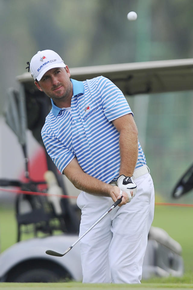 Graeme McDowell of Northern Ireland watches his shot from the rough on the eighth hole during the second round of the EurAsia Cup golf tournament at the Glenmarie Golf and Country Club in Subang, Malaysia, Friday, March 28, 2014. (AP Photo/Joshua Paul)