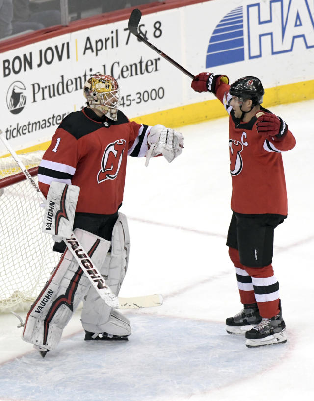 New Jersey Devils goaltender Keith Kinkaid celebrates with Andy Greene, right, after the Devils defeated the Carolina Hurricanes 4-3 in an NHL hockey game Tuesday, March 27, 2018, in Newark, N.J. (AP Photo/Bill Kostroun)