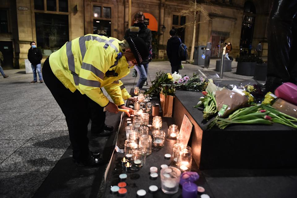 NOTTINGHAM, ENGLAND - MARCH 13: A female police officer lights a candle next to a makeshift memorial during a vigil for Sarah Everard, following her kidnap and murder, on Market Square on March 13, 2021 in Nottingham, England. Vigils are being held across the United Kingdom in memory of Sarah Everard. Yesterday, the Police confirmed that the remains of Ms Everard were found in a woodland area in Ashford, a week after she went missing as she walked home from visiting a friend in Clapham. Metropolitan Police Officer Wayne Couzens has been charged with her kidnap and murder. (Photo by Nathan Stirk/Getty Images)