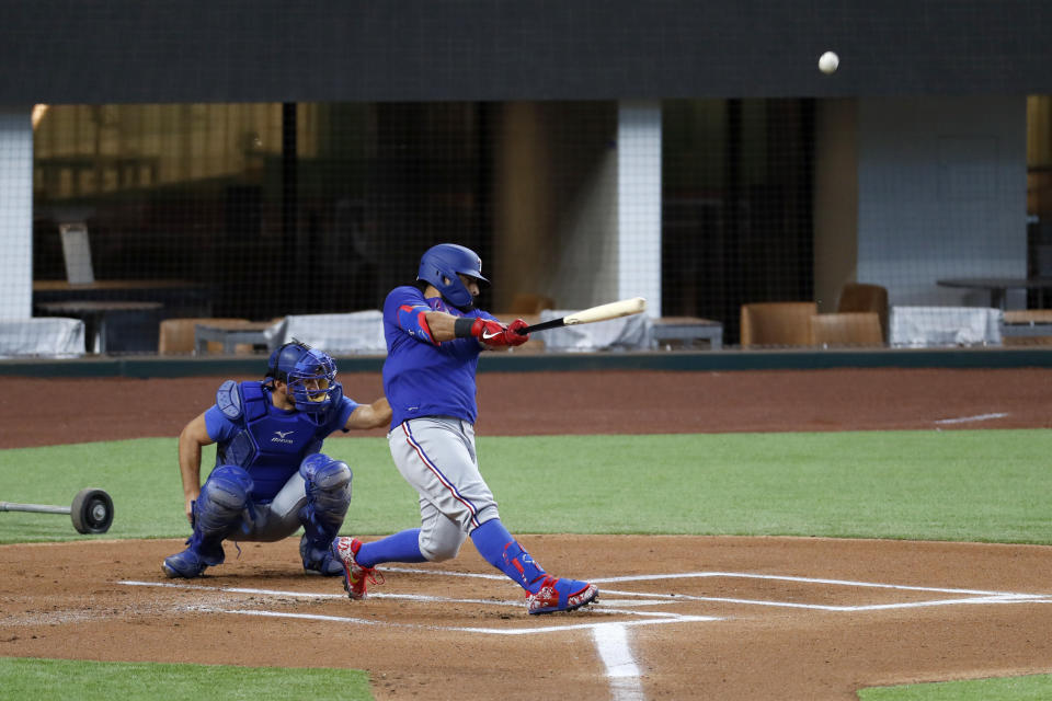Texas Rangers' Rougned Odor connects for a home run during a baseball practice as catcher Jeff Mathis looks on at Globe Life Field in Arlington, Texas, Friday, July 3, 2020. (AP Photo/Tony Gutierrez)