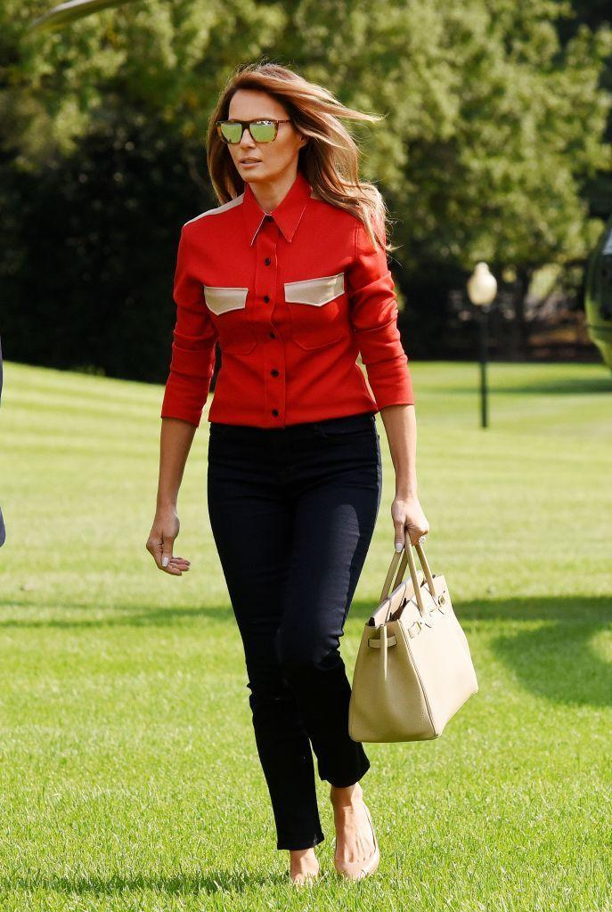 <p>Departing Marine One from her return trip from Camp David, FLOTUS sported a fire engine red blouse with dark pants, a nude tote, and sunglasses. </p>