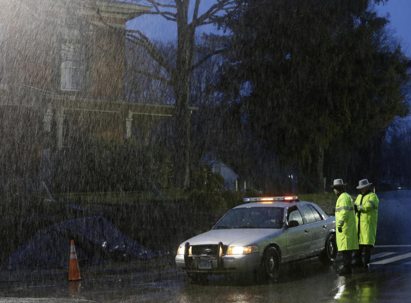 FILE - In this Dec. 21, 2012 file photo, Connecticut State Police confer in the rain at the intersection of a closed road in the Sandy Hook village of Newtown, Conn.   In a first-of-its-kind program, the Connecticut State Police assigned troopers to each victim's family to help with whatever they needed after the shooting tragedy.  The detail ended officially with the funerals, but many of the officers are staying in close contact with the families they helped through the tragedy. (AP Photo/Seth Wenig, File)