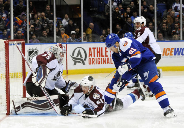 Colorado Avalanche goalie Jean-Sebastien Giguere (35) defends as Andre Benoit (61) falls to the ice against New York Islanders' Kyle Okposo (21) in the second period of an NHL hockey game on Saturday, Feb. 8, 2014, in Uniondale, N.Y. (AP Photo/Kathy Kmonicek)