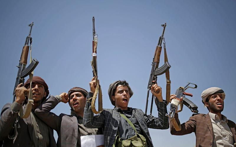 Shiite Houthi tribesmen hold their weapons as they chant slogans during a tribal gathering showing support for the Houthi movement, in Sanaa, Yemen, last year. - AP