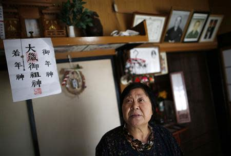 Kimiko Koyama, 69, who evacuated from the Miyakoji area of Tamura three years ago, looks up inside her house with portraits of her deceased parents in the background, after she returned to her home with her husband Toshio, 76, in Tamura, Fukushima prefecture April 1, 2014. REUTERS/Issei Kato