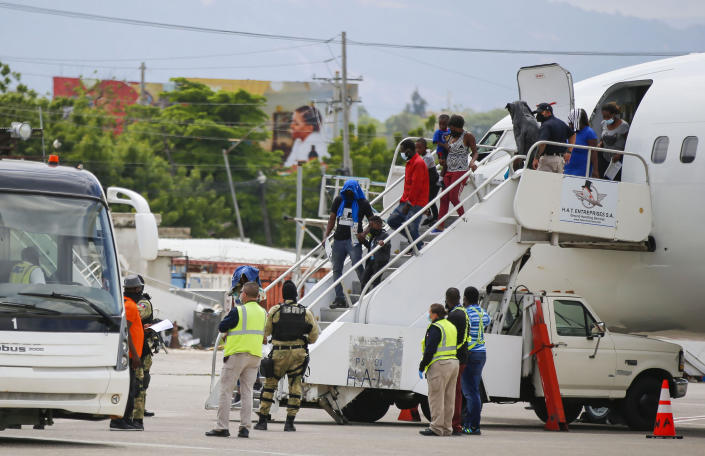 Haitians who were deported from the United States deplane at the Toussaint Louverture International Airport, in Port au Prince, Haiti, Sunday, Sep. 19, 2021. Thousands of Haitian migrants have been arriving to Del Rio, Texas, to ask for asylum in the U.S., as authorities begin to deported them to back to Haiti. (AP Photo/Joseph Odelyn)