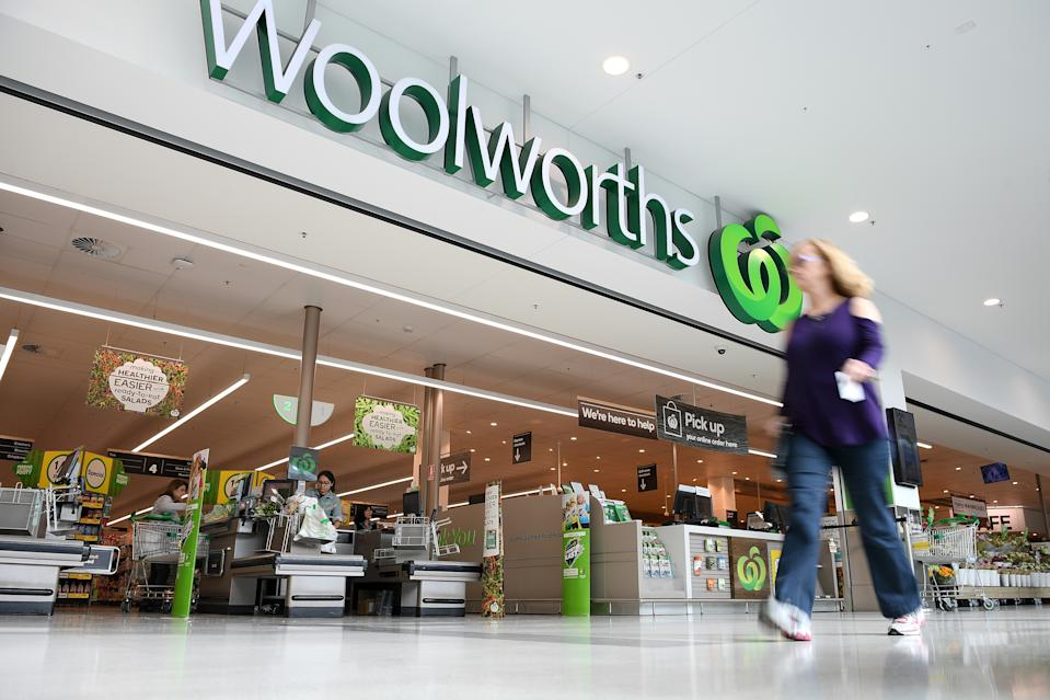 A woman is shown walking in front of a Woolworths supermarket.
