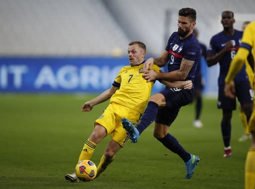 France's Olivier Giroud, right, and Sweden's Sebastian Larsson fight for the ball during the UEFA Nations League soccer match between France and Sweden at the Stade de France stadium in Saint-Denis, northern Paris, Tuesday, Nov. 17, 2020. (AP Photo/Francois Mori)