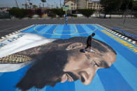 FILE - In this April 17, 2019 file photo, mural artist Gustavo Zermeno Jr. walks on a basketball court mural he dedicated to slain rapper Nipsey Hussle in Los Angeles. Hussle, 33, was shot and killed outside his Los Angeles clothing store on March 31, 2019. A year after Hussle's death, his popularity and influence are as strong as ever. He won two posthumous Grammys in January, he remains a favorite of his hip-hop peers and his death has reshaped his hometown of Los Angeles in some unexpected ways. (AP Photo/Jae C. Hong, File)