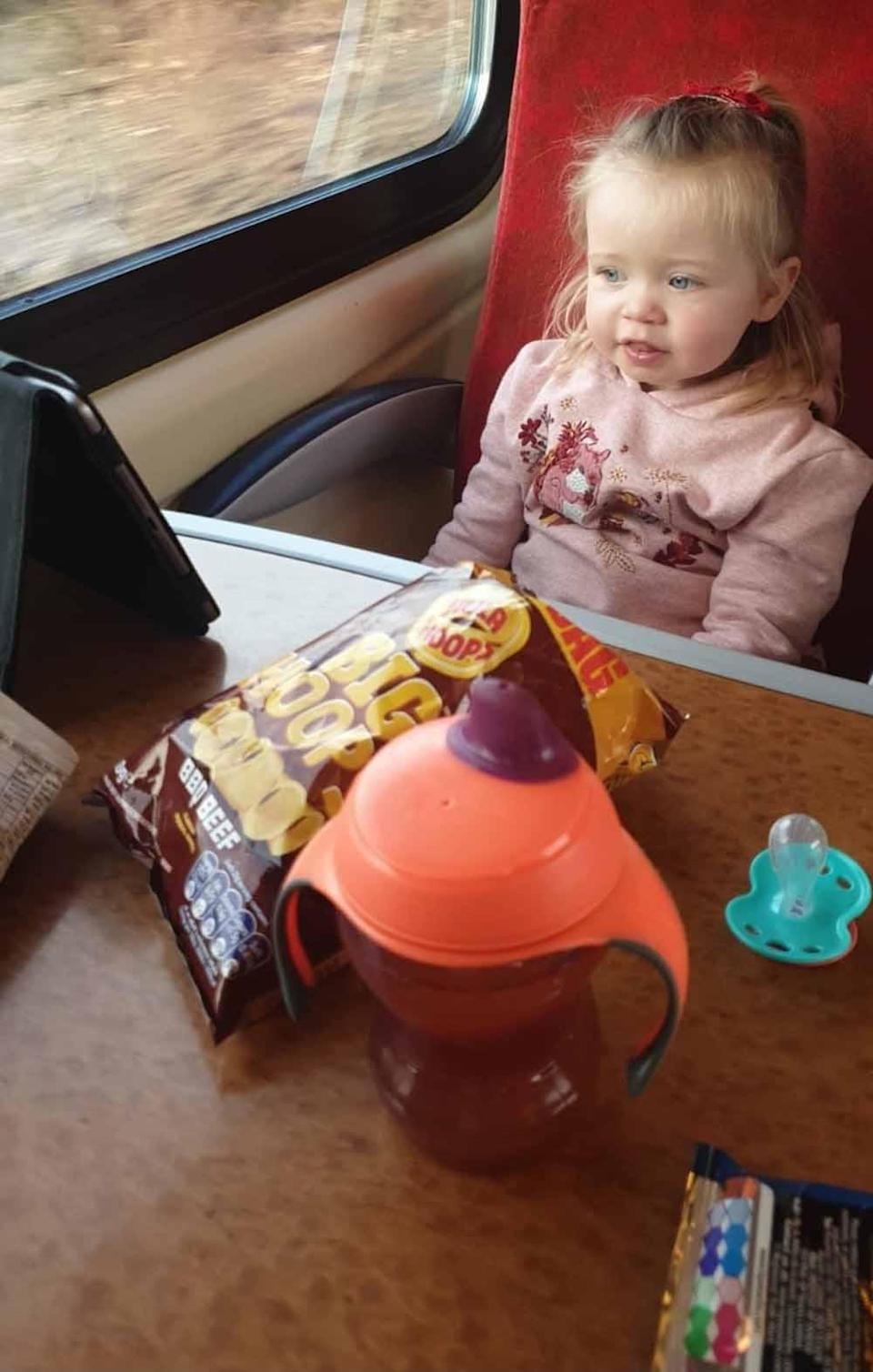 Evie on the train to her first treatment in Birmingham. PA REAL LIFE COLLECT