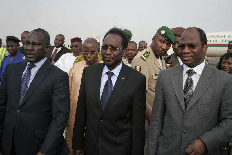 Dioncounda Traore, center, Mali's parliamentary head who was forced into exile after last month's coup, walks with Burkina Faso's Foreign Affairs Minister Djibrill Bassole, right, as Traore arrives at the airport to take up his constitutionally-mandated post as interim president, in Bamako, Mali Saturday, April 7, 2012. Junta spokesman Lt. Amadou Konare, second right, looks on. Traore's return comes after coup leader Capt. Amadou Haya Sanogo signed an accord late Friday, agreeing to return the nation to constitutional rule.(AP Photo/Harouna Traore)