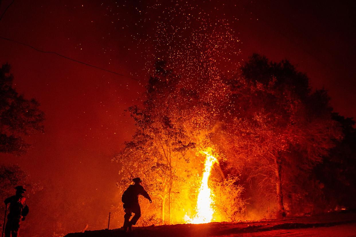 Firefighters monitor a backfire during the Carr fire in Redding, California on July 27, 2018.