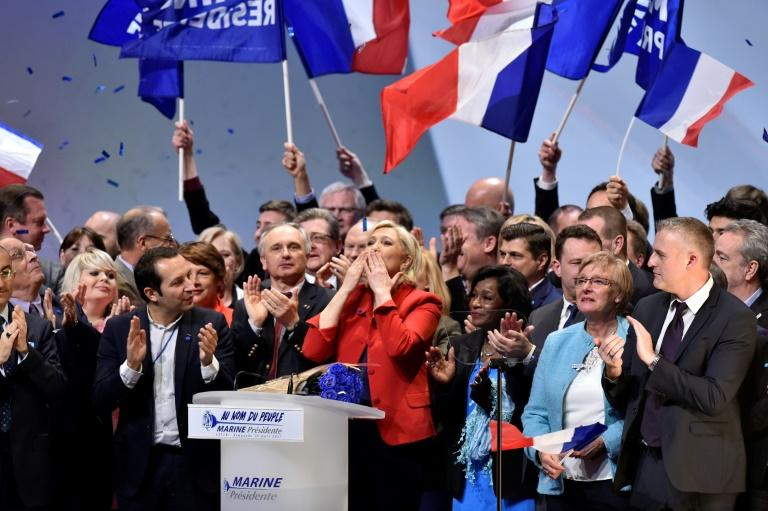 French presidential election candidate for the far-right Front National party Marine Le Pen (C) acknowledges applause after she delivered a speech during a rally at the Zenith venue on March 26, 2017 in Lille