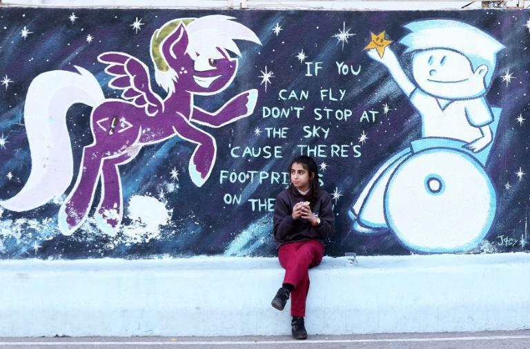 An Iraqi Christian student sits in front of a a mural in a playground at a school in the Jordanian capital Amman