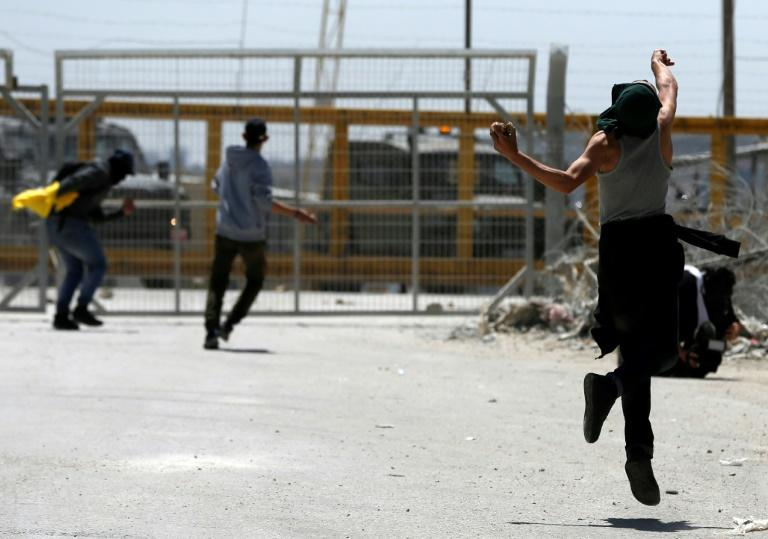 Palestinian protesters hurl stones towards Israeli security forces during clashes following a demonstration in solidarity with hunger-striking Palestinian prisoners, in front of Ofer prison in the West Bank, on April 20, 2017