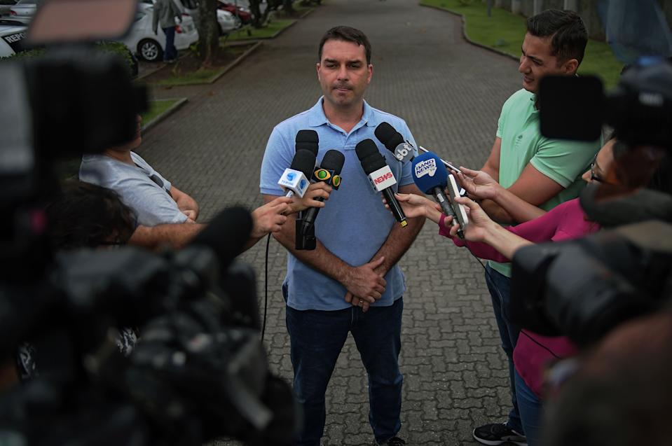 Flavio Bolsonaro (C), the son of Brazil's right-wing presidential candidate for the Social Liberal Party (PSL) Jair Bolsonaro, talks to the media outside his father's residence in Rio de Janeiro, Brazil, on October 8, 2018. - A deeply polarized Brazil stood at a political crossroads on october 8, 2018 as the bruising first round of the presidential election left voters with a stark choice in the run-off between far-right firebrand Jair Bolsonaro and leftist Fernando Haddad. Bolsonaro won 46 percent of the vote to Haddad's 29 percent, according to official results. (Photo by CARL DE SOUZA / AFP)        (Photo credit should read CARL DE SOUZA/AFP via Getty Images)