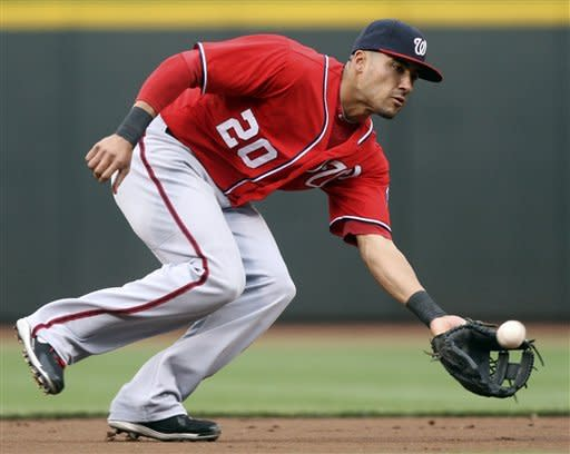 Washington Nationals shortstop Ian Desmond fields a ground ball hit by Cincinnati Reds' Drew Stubbs in the first inning of a baseball game, Saturday, May 12, 2012, in Cincinnati. Reds' Zack Cozart was safe at second and Stubbs was safe at first on the fielders choice. (AP Photo/Al Behrman)