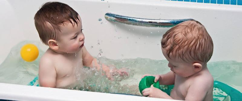 Two-year-old twins play a bathroom