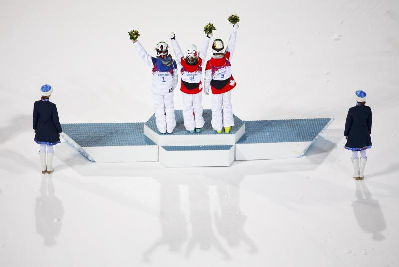 Third placed Kearney of the U.S., winner Canada's Justine Dufour-Lapointe and her second placed sister Chloe wave during flowers ceremony after the women's freestyle skiing moguls final competition at the 2014 Sochi Winter Olympic Games in Rosa Khutor