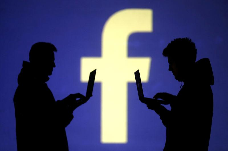FILE PHOTO: Silhouettes of laptop users are seen next to a screen projection of Facebook logo in this picture illustration