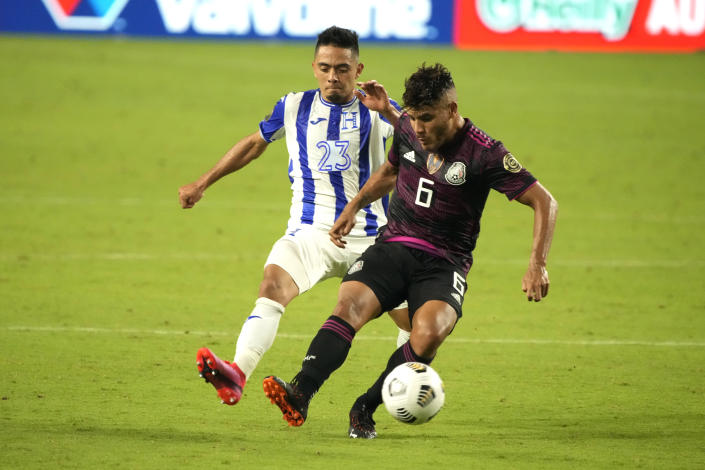 Mexico midfielder Jonathan Dos Santos (6) shields the ball from Honduras defenseman Diego Rodriguez during the second half of a CONCACAF Gold Cup soccer match Saturday, July 24, 2021, in Glendale, Ariz. (AP Photo/Rick Scuteri)