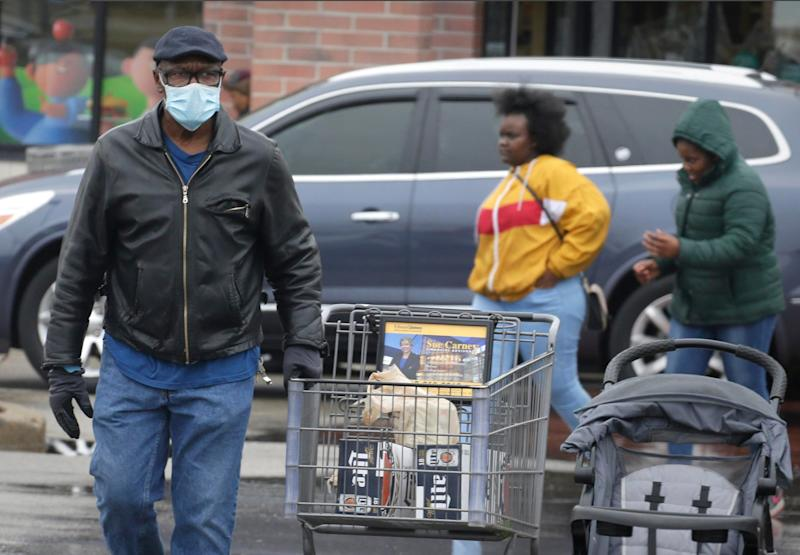 A man covers his face with a mask while shopping at Pick 'N Save March 29 in a neighborhood listed as a hot spot for coronavirus, according to a map by the Milwaukee County Office of Emergency Management.