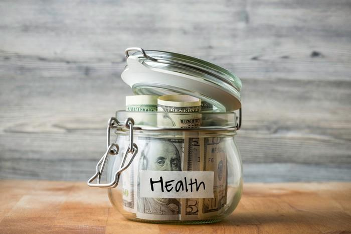 """Glass jar filled with various denominations of dollar bills and labelled """"Health."""""""