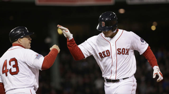 Boston Red Sox's Xander Bogaerts, right, is congratulated by first base coach Arnie Beyeler (43) after his sacrifice fly during the eighth inning of Game 1 of baseball's World Series against the St. Louis Cardinals Wednesday, Oct. 23, 2013, in Boston. (AP Photo/David J. Phillip)