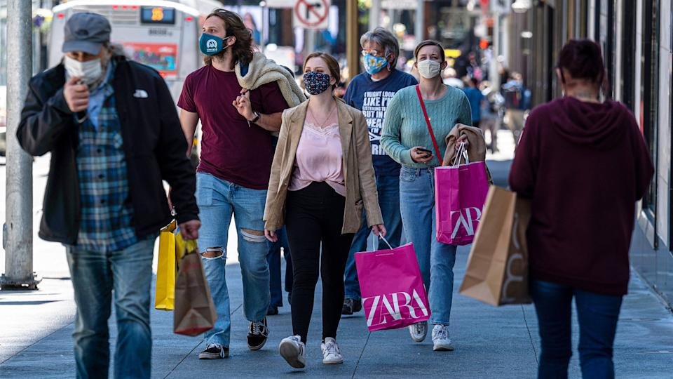 People on a sidewalk wearing protective masks and carry shopping bags