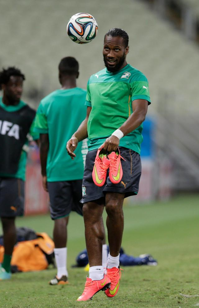 Ivory Coast's Didier Drogba heads a ball during on official training session the day before the group C World Cup soccer match between Greece and Ivory Coast at the Arena Castelao in Fortaleza, Brazil, Monday, June 23, 2014. Ivory Coast should beat Group C strugglers Greece, but even a draw won't hold them back as long as Japan doesn't upset Colombia. (AP Photo/Fernando Llano)