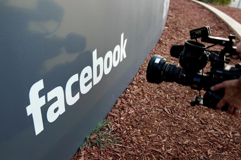 FILE- In this May 18, 2012, file photo a television photographer shoots the sign outside of Facebook headquarters in Menlo Park, Calif. S&P Dow Jones Indices is shuffling the line-up of three of the 11 groups that make up the benchmark S&P 500 index. On Monday, 20 companies in the index including famous names like Facebook, Alphabet and Netflix will find a new home. (AP Photo/Paul Sakuma, File)