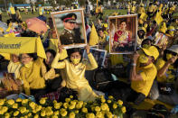 Supporters of Thai monarch display images of the late King Bhumibol Adulyadej ahead of the arrival of King Maha Vajiralongkorn and Queen Suthida to participate in a candle lighting ceremony to mark birth anniversary of late King Bhumibol Adulyadej at Sanam Luang ceremonial ground in Bangkok, Thailand, Saturday, Dec. 5, 2020. (AP Photo/Gemunu Amarasinghe)
