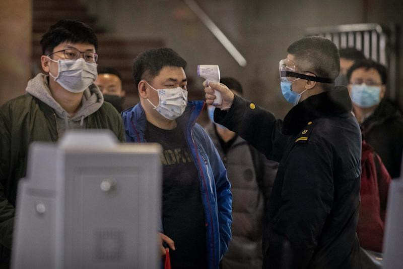 A Chinese passenger checked for a fever by a health worker at a Beijing railway station (Getty Images)