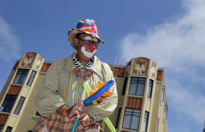 """""""Kenny the Clown,"""" otherwise known as Kenneth Kahn, smiles as he hands out balloons in San Francisco, Friday, Aug. 17, 2012. Kahn says he unwittingly received a stolen iPad from a friend who was later arrested for breaking into former Apple CEO Steve Jobs' residence in Palo Alto. Kahn said he had the stolen iPad for a few days before police came asking for the purloined tablet, which was returned to the Jobs family. The professional entertainer said he never examined the device's contents. Instead he downloaded the """"Pink Panther"""" and other songs to play while entertaining kids and tourists during his clown routine. Kahn said had no idea where the 64GB iPad came from until his friend, 35-year-old Kariem McFarlin of Alameda, Calif., was arrested Aug. 2. (AP Photo/Marcio Jose Sanchez)"""