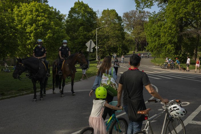 A family walks through New York's Prospect Park, May 16, 2020. (Benjamin Norman/The New York Times)